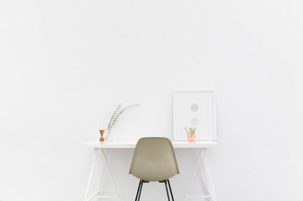 Table en plastique recyclé blanche avec une chaise kaki vide. Sur cette table il y a des petites plantes et un tableau